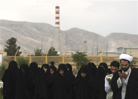 An Iranian cleric prays as a prayer leader for female students before a ceremony to form a human chain around UCF to show their support for Iran's nuclear programme in Isfahan